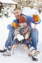 Vater und Sohn, die auf Schlitten sitzen Stockfoto