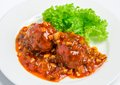 Veal meatballs with bacon in a tomato sauce with mushrooms on white plate Stock Photography