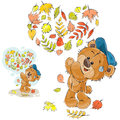 Vector autumn illustration of a brown teddy bear threw up the fallen leaves and made a heart out of them Royalty Free Stock Photo