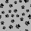 Vector illustration of a seamless pattern of black wild animal paws on a gray background