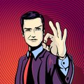 Vector illustration of successful businessman gives ok in vintage pop art comics style likes and positive feel gesture good agree Royalty Free Stock Photo
