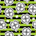 Vector seamless pattern with dotted lucky four leaf clover or shamrock in black on the striped green. Holiday background. Royalty Free Stock Photo