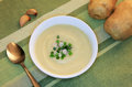 Vegan garlic and potato soup with chopped green onion garnish Stock Images