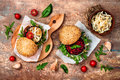 Vegan grilled eggplant, arugula, sprouts and pesto sauce burger. Veggie beet and quinoa burger. Top view, overhead, flat lay. Royalty Free Stock Photo