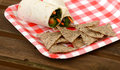 Vegan wrap and tortilla chips on red white checkered plate Stock Photography