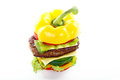 Vegetable burger stacked colorful yellow red green and beef top Royalty Free Stock Image