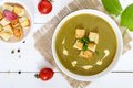Vegetable cream soup with spinach and potatoes in a white bowl with garlic croutons on a dark wooden background. Royalty Free Stock Photo