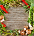 Vegetable frame of fresh vegetables and herbs on a wooden background Royalty Free Stock Photo