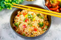 Vegetable fried rice in black bowl with capsicum spring onion green peas broccoli Stock Photography