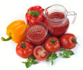 Vegetable juice with ingredients tomatoes peppers basil Stock Photos