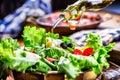 Vegetable lettuce salad. Olive oil pouring into bowl of salad. Italian Mediterranean or Greek cuisine. Vegetarian vegan food Royalty Free Stock Photo