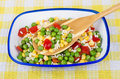 Vegetable mix in bowl and spoon on plaid tablecloth blue bamboo yellow Stock Photo