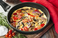 Vegetable omelet in skillet cooked a or frypan mushrooms capsicum baby plum tomatoes and red onion Royalty Free Stock Photo