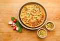 Vegetable quiche tart in tray countertop fresh out of the oven on round with two smaller quichelets on the side and radishes on Royalty Free Stock Photos