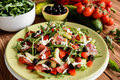 Vegetable salad with Black Forest ham, arugula, cucumber, black olives, red pepper, tomato and Mozzarella Royalty Free Stock Photo