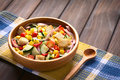 Vegetable salad fresh made of sweet corn cherry tomato cucumber red onion red pepper chives with croutons in wooden bowl Royalty Free Stock Image
