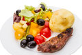 Vegetable salad with olives and meat fried on a white plate Royalty Free Stock Image
