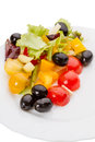 Vegetable salad with olives on a white plate Stock Photography