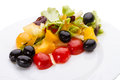 Vegetable salad with olives on a white plate Royalty Free Stock Image