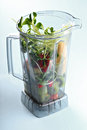 Vegetables in a blender on pale blue background Royalty Free Stock Images
