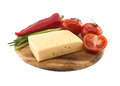 Vegetables and cheese on cutting board, isolated on white backgr Royalty Free Stock Photo