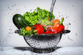 Vegetables in a colander under running water Royalty Free Stock Photo