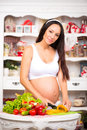 Vegetables and diet during pregnancy. Beautiful pregnant woman in the kitchen preparing a meal Royalty Free Stock Photo