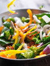Vegetables falling into a stir fry wok close up stock motion photo of Stock Photography