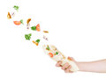 Vegetables fly to pita bread which keeps a hand on a white back background Stock Photos