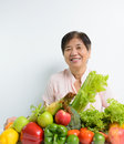 Vegetables and fruits elderly woman with pile of Royalty Free Stock Photo