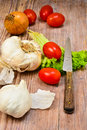 Vegetables with garlic knife and tomatoes on wooden table Stock Photos