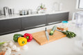 Vegetables with knife and chopping board on kitchen counter Royalty Free Stock Photo