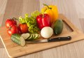 Vegetables and knife on cutting board Royalty Free Stock Images