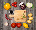 Vegetables and spices and empty old cutting board. Colorful ingr Royalty Free Stock Photo