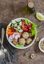 Vegetarian buddha bowl - quinoa meatballs and vegetable salad on wooden background, top view. Healthy, vegetarian food Royalty Free Stock Photo