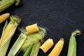 Vegetarian food. Corn cobs on black stone background top view copyspace