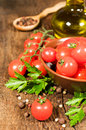 Vegetarian food still life with fresh cherry tomatoes parsley olive oil and spices Stock Images