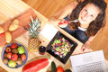 Vegetarian information online for vegetarians a young girl eating salad while using a laptop Royalty Free Stock Images