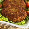 Vegetarian lentil burger made of brown lentils and grated carrots served on lettuce selective focus focus on the front of the Royalty Free Stock Images