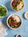 Vegetarian lunch table in the asian style bowls with rice noodles vegetable stir fry on a blue background top view Stock Photography