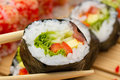 Vegetarian sushi roll in chopsticks with made dish on background Royalty Free Stock Image