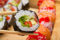 Vegetarian sushi roll in chopsticks with made dish on background Royalty Free Stock Photography