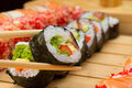 Vegetarian sushi roll in chopsticks with made dish on background Stock Photography