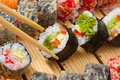 Vegetarian sushi roll in chopsticks with made dish on background Stock Images