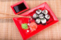 Vegetarian sushi roll served in a form of flower on a red plate on a bamboo mat Stock Photography