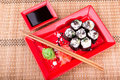 Vegetarian sushi roll served in a form of flower on a red plate on a bamboo mat Stock Photos