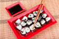 Vegetarian sushi roll served on a red plate on a bamboo mat Royalty Free Stock Image