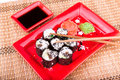 Vegetarian sushi roll served on a red plate in form of flower bamboo mat Royalty Free Stock Image
