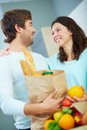 Vegetarians young couple with paperbags looking at one another with smiles Stock Photo