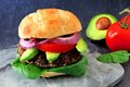 Veggie burger with avocado and spinach on a dark background Royalty Free Stock Photo
